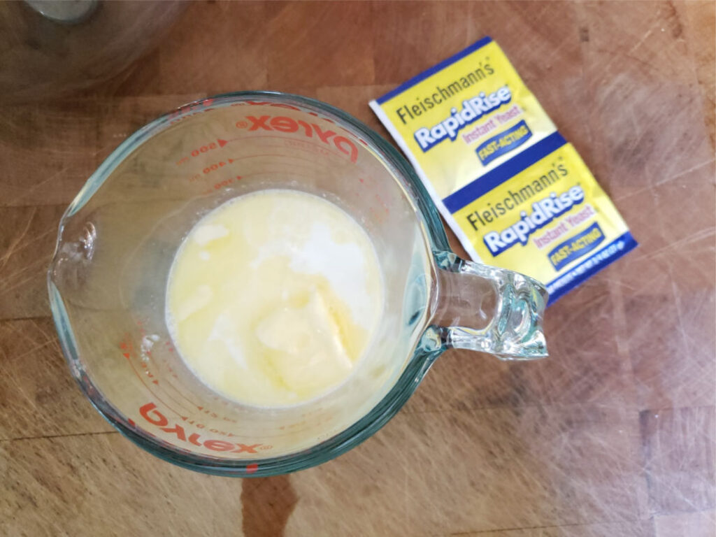 milk, water, and butter in glass measuring cup on butcher block
