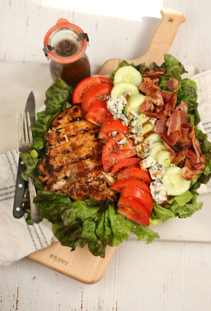 Grilled Chicken, chunks of bacon, sliced tomatoes, cucumbers, and blue cheese on green leaf lettuce on serving plate