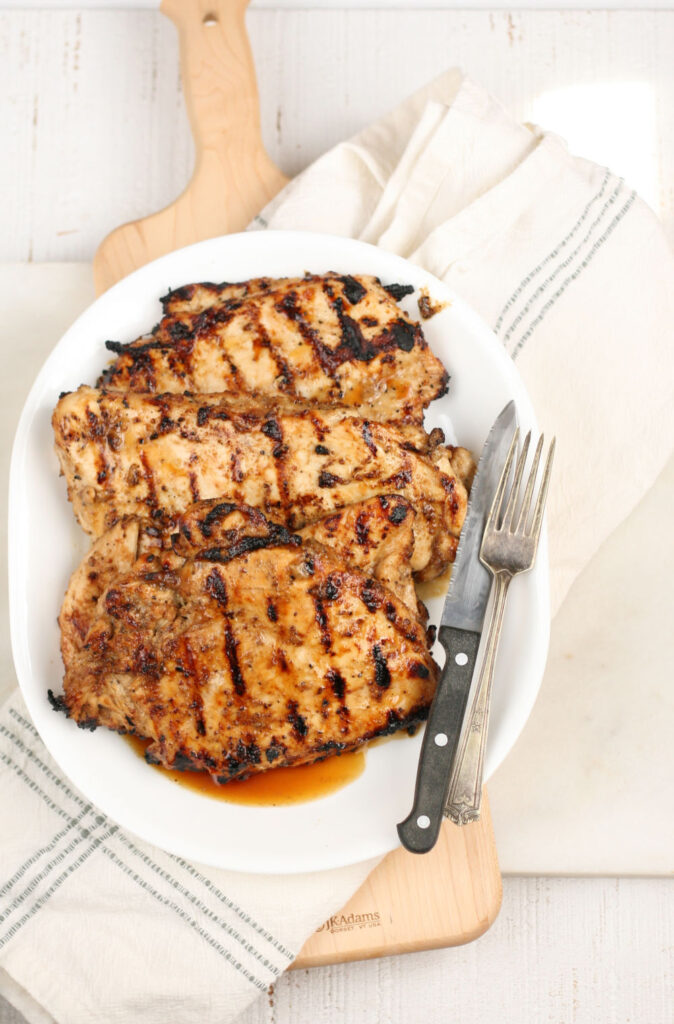 grilled chicken breasts on a white oval serving plate with fork and knife on right side of plate