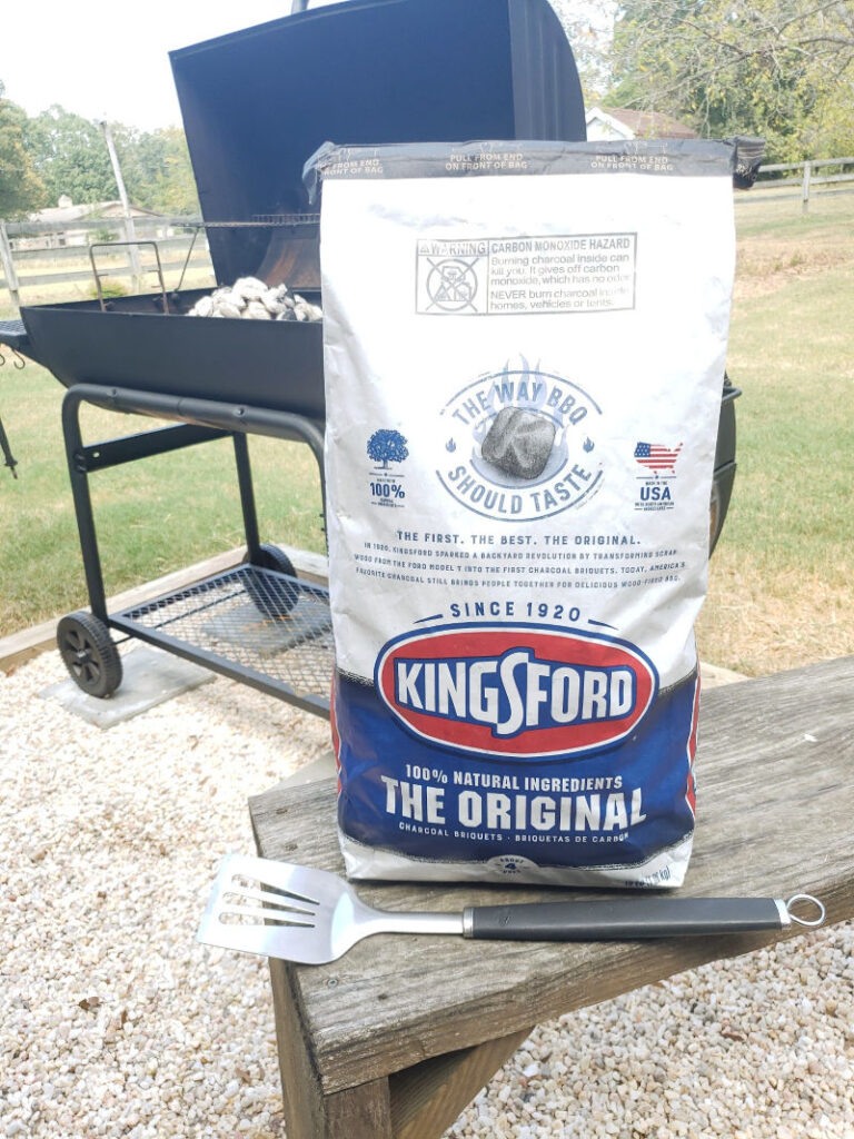 Bag of Kingsford Charcoal on wooden bench in front of charcoal grill
