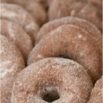 apple cider doughnuts rolled in cinnamon sugar, stacked up against each other
