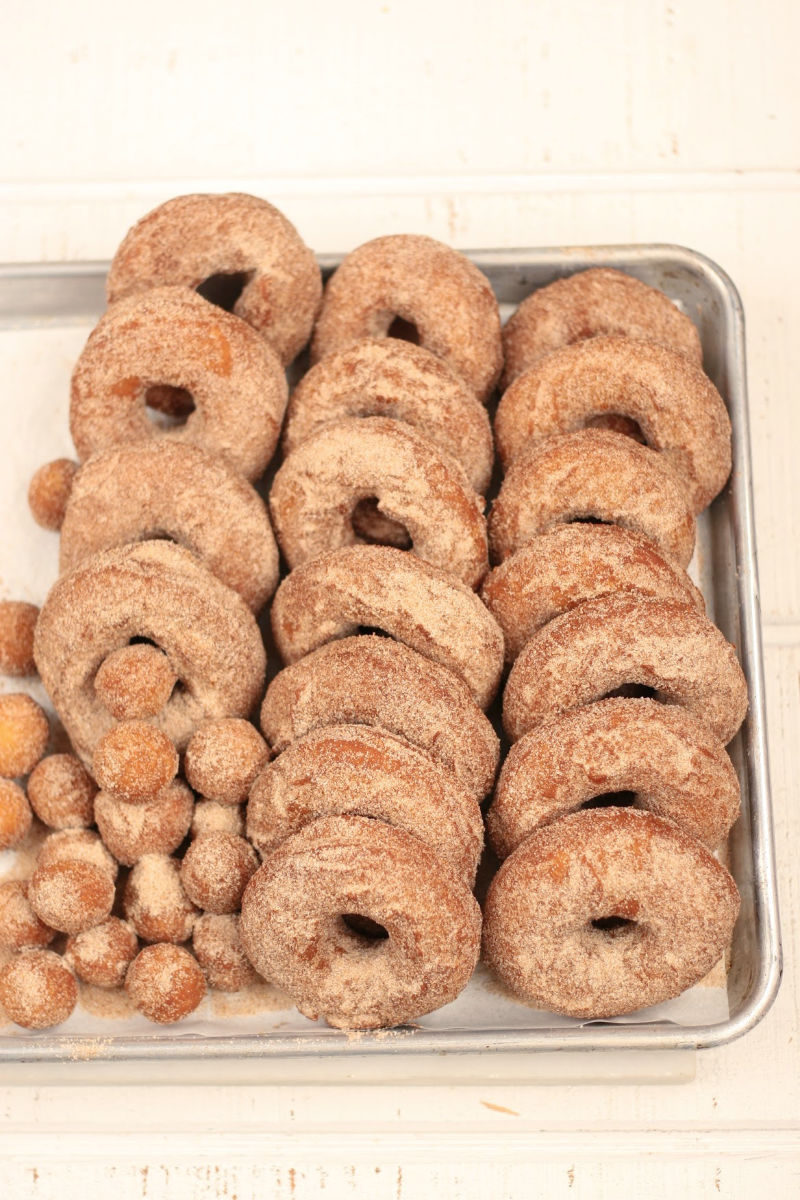 apple cider donuts stacked against each other on a half sheet pan