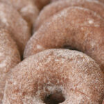 apple cider donuts rolled in cinnamon sugar, stacked against each other on baking tray
