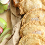 Five apple hand pies leaning against each other on wooden cutting board, loose apple slices around.