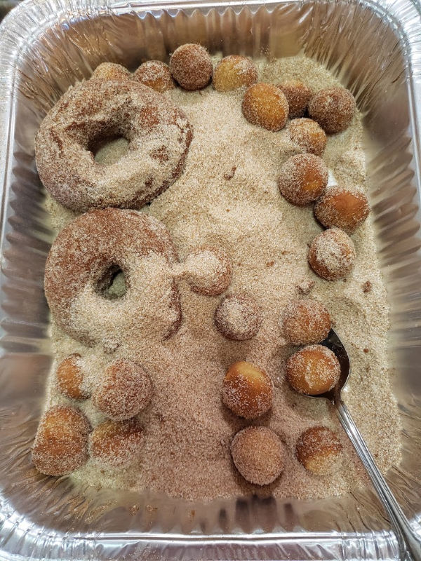 rollling doughnuts in cinnamon sugar mixture