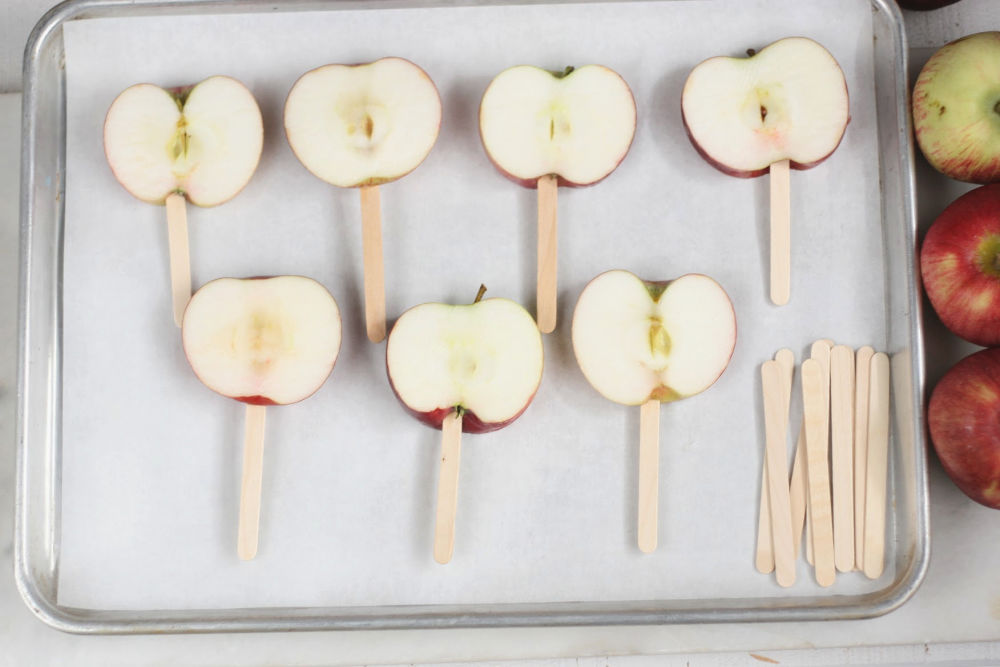 slices of apples on sticks on half sheet pan lined with parchment paper