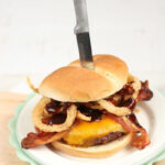 bacon cheeseburger with buttermilk onion rings on plate with knife through bun