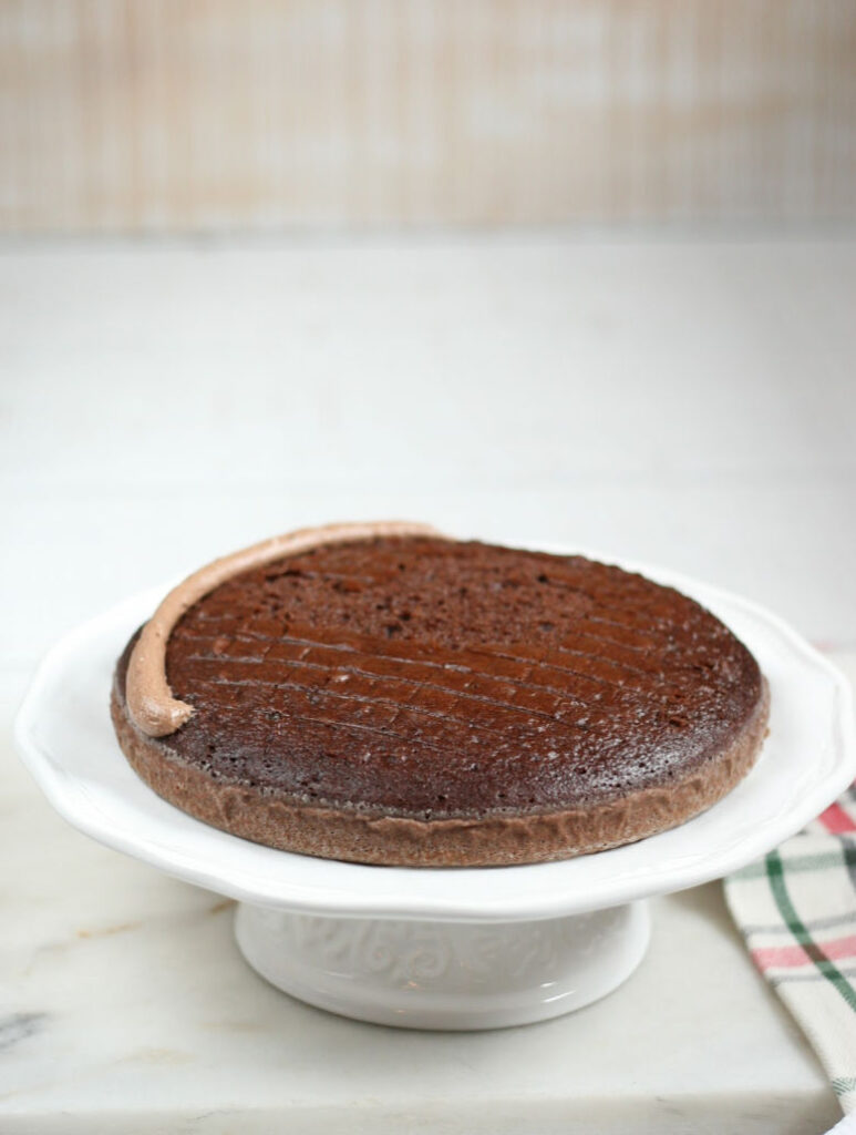 chocolate cake layer on a white footed cake dish