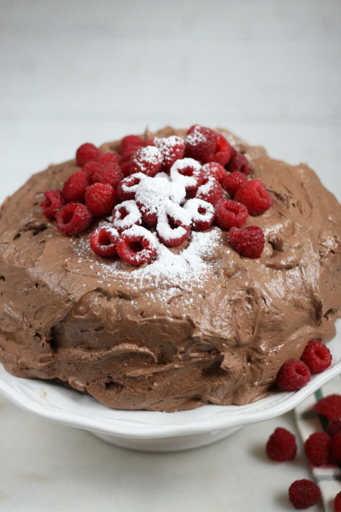 chocolate cake with chocolate frosting on white footed cake dish, topped with fresh raspberries and powdered sugar