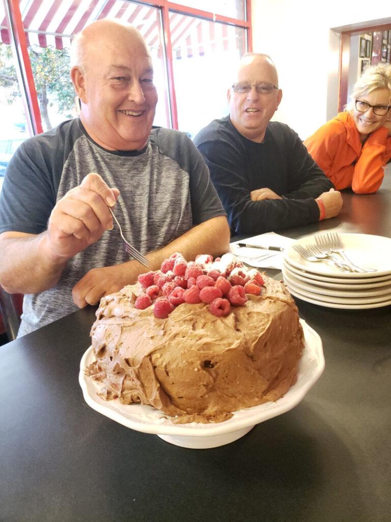 layered chocolate cake with people enjoying