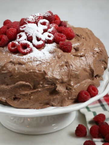 chocolate frosting on chocolate cake with fresh raspberries on top