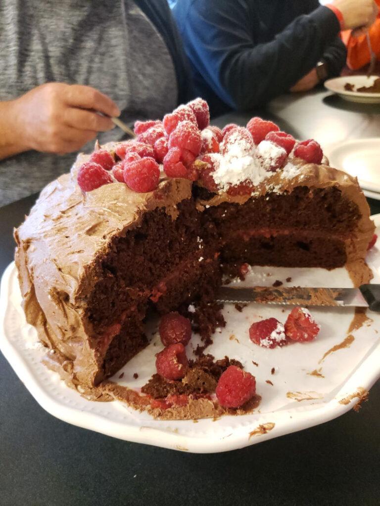 sliced chocolate cake with raspberries on top