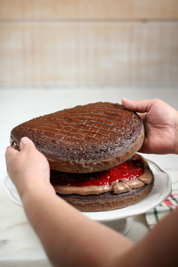 placing chocolate cake on top of raspberry filling on another chocolate cake layer