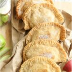 fried apple hand pies on a wooden cutting board, drying on brown paper lunch bag, loose pieces of apples around them