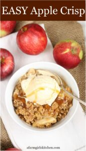 apple crisp in bowl topped with vanilla ice cream, drizzled with caramel sauce
