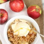apple crisp in white bowl, topped with vanilla ice cream and caramel sauce