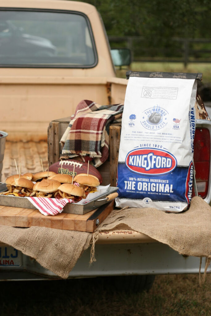 back of pickup truck tailgate with cheeseburgers and football items