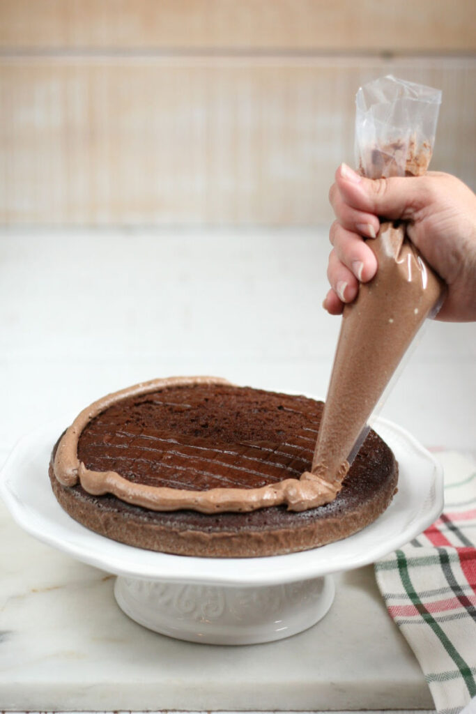Piping chocolate frosting on chocolate layered cake