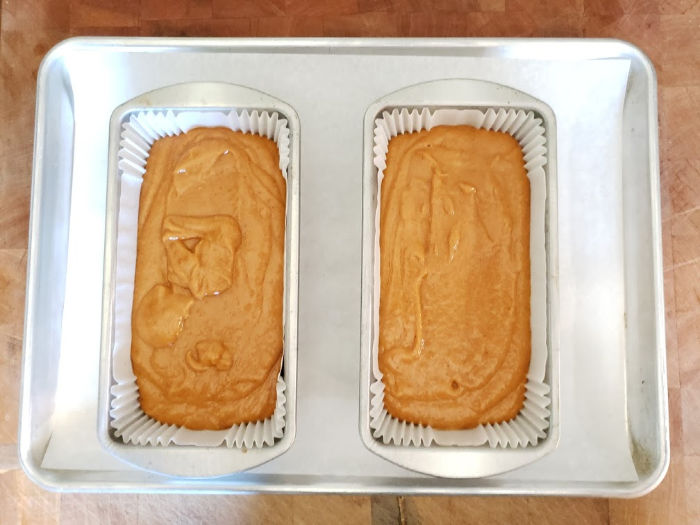 pumpkin cake batter in metal loaf pans with paper liners on a half sheet pan lined with parchment paper