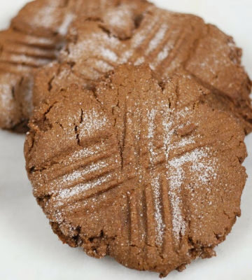 Molasses cookies stacked against each other on a piece of white marble