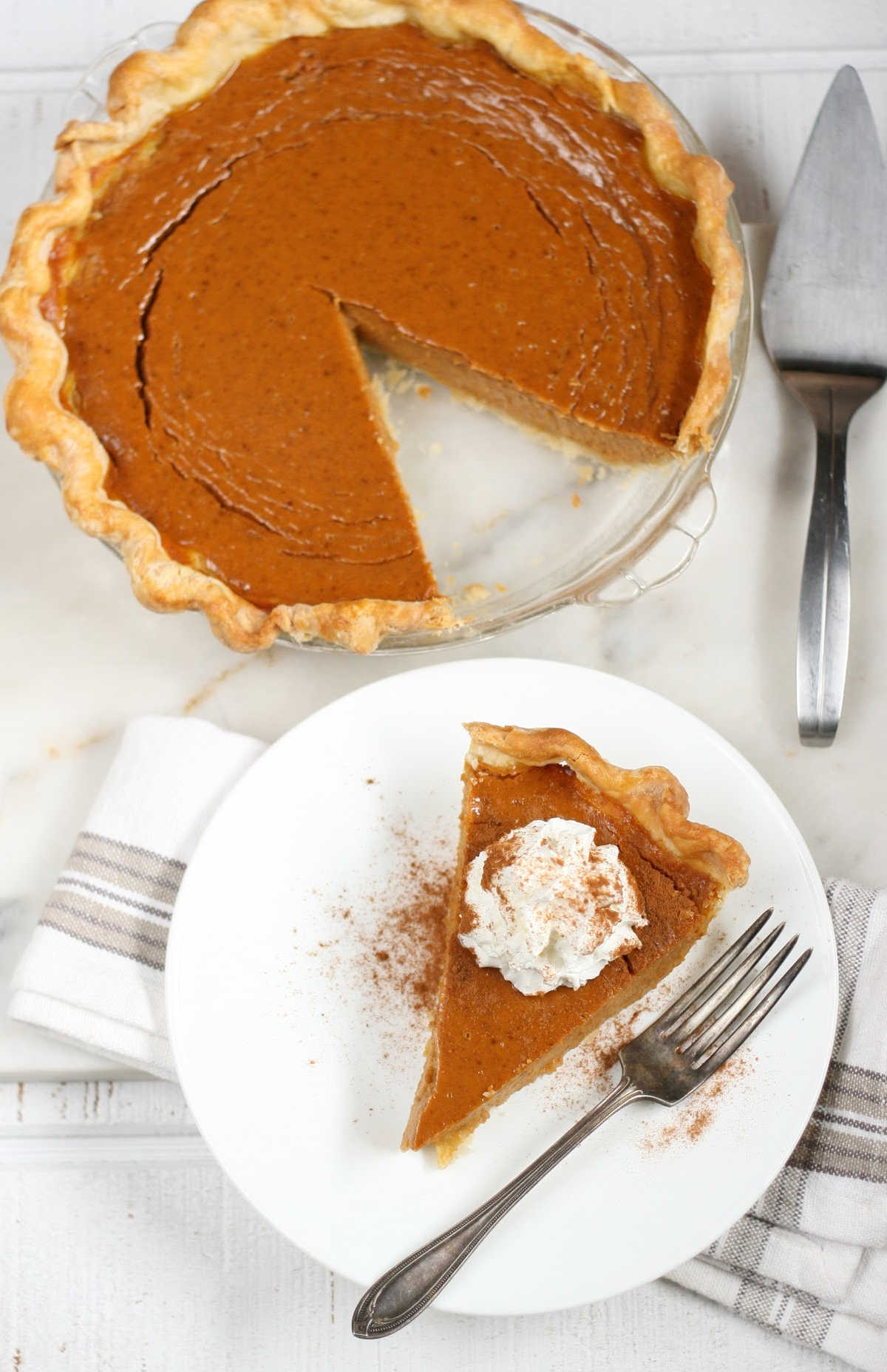 slice of pumpkin pie on small white plate, full pie background.