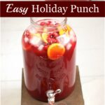 Holiday punch of cranberry juice, pineapple juice, and lemon lime soda in a glass drink dispenser. Orange slices and fresh cranberries in the punch
