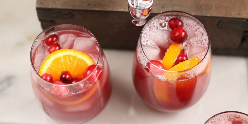 stemless wine glasses with holiday punch, ice cubes, orange slices, and fresh cranberries