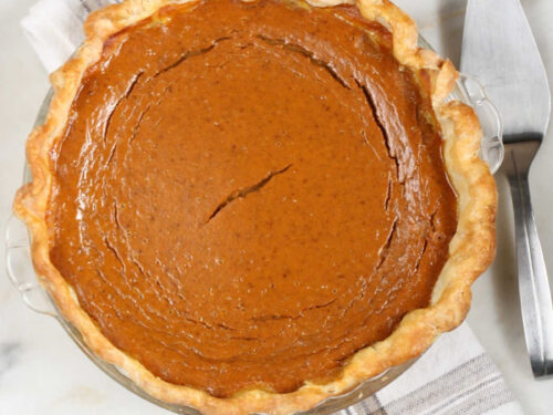 pumpkin pie on white washed wood, metal pie server to right.