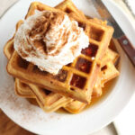 square waffles stacked on top of each other, topped with whipped cream, dusted with cinnamon