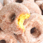 pumpkin donuts on top of each other on cutting board