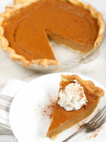 Pumpkin pie with slice cut out in glass pie dish, slice of pie on small white plate.