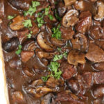 white rectangle baking dish with beef tips with mushroom gravy