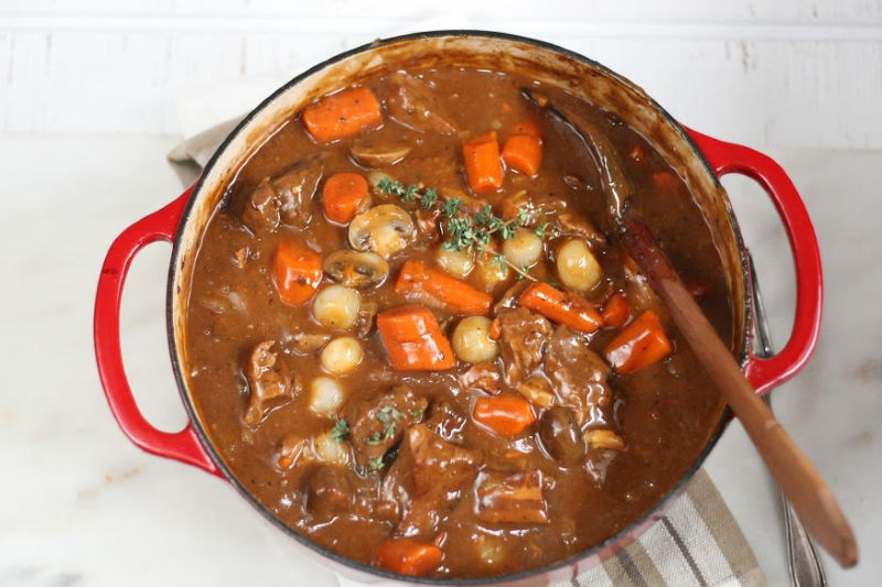 Red Dutch oven with Beef Bourguignon, carrots, mushrooms, pearl onions, topped with a fresh sprig of thyme