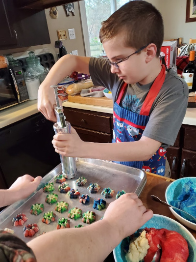 Little boy making Spritz cookies with vintage cookie press