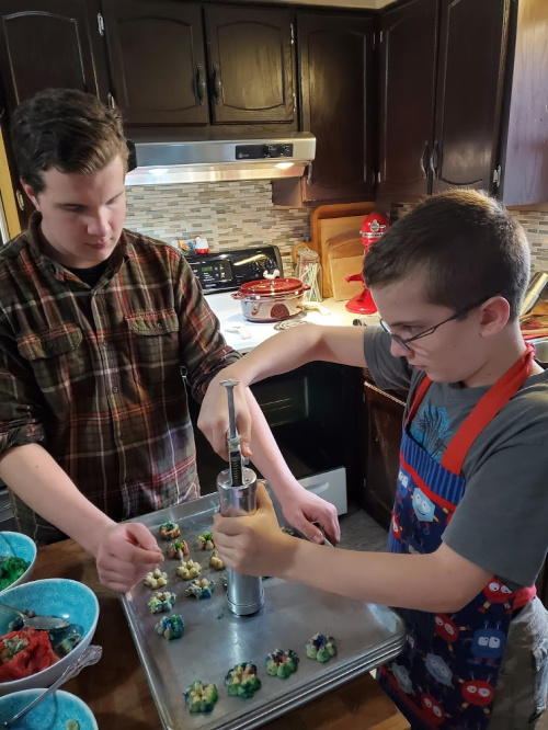 Kids helping each other making Spritz cookies on sheet pans