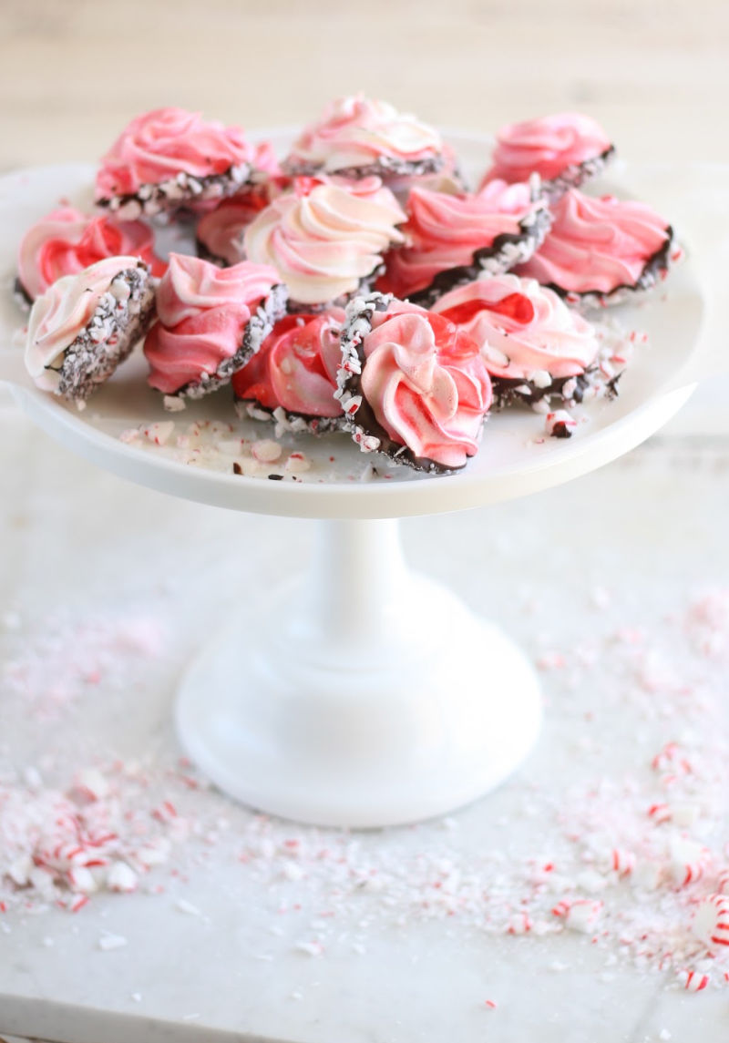 meringue cookies on white footed glass cake dish