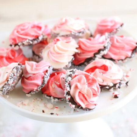 meringue cookies dipped in chocolate, rolled in crushed peppermints, on white footed cake dish