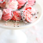 Pink and red swirled meringue cookies dipped in chocolate, rolled in crushed peppermints on glass footed cake dish