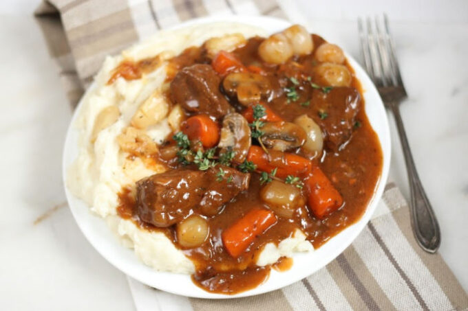 Boeuf Bourguignon and mashed potatoes on white plate, fork to the right
