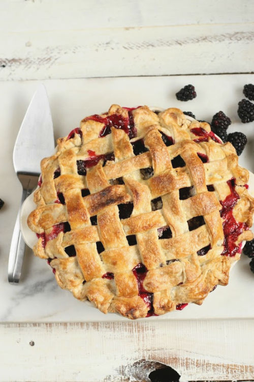 blackberry pie with lattice crust on white marble