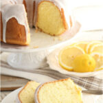Lemon Bundt cake with lemon icing on white footed cake dish, small white plate with two slices of cake in front