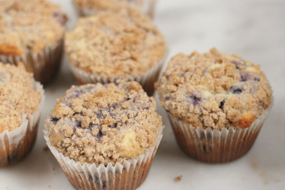 Blueberry muffins with crumb topping on white marble