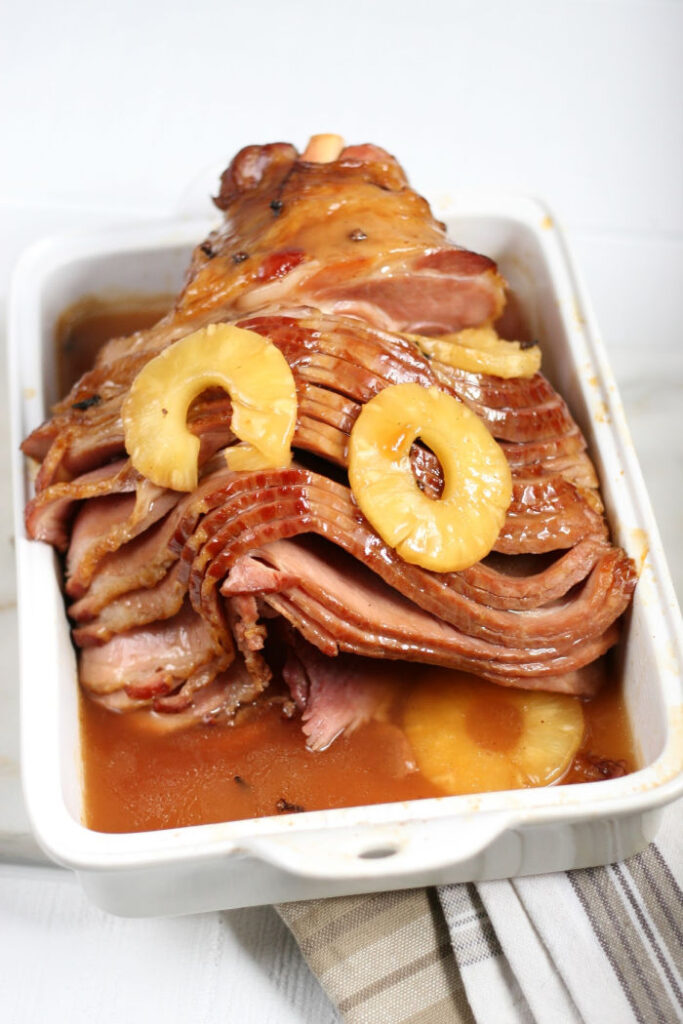 spiral sliced ham in white rectangle ceramic baking dish, with pineapple slices