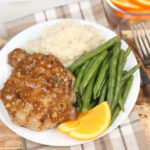 grilled pork chops on white plate with green beans, mashed potatoes, and slices of oranges