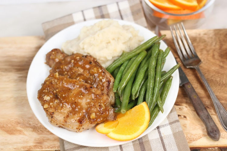 glazed pork chops on white plate with fresh green beans and mashed potatoes
