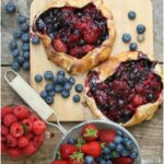 mixed berry galettes on reclaimed barn boards with metal strainer filled with fresh berries to side