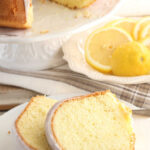 Lemon Bundt cake on white footed cake dish, two slices out of cake.