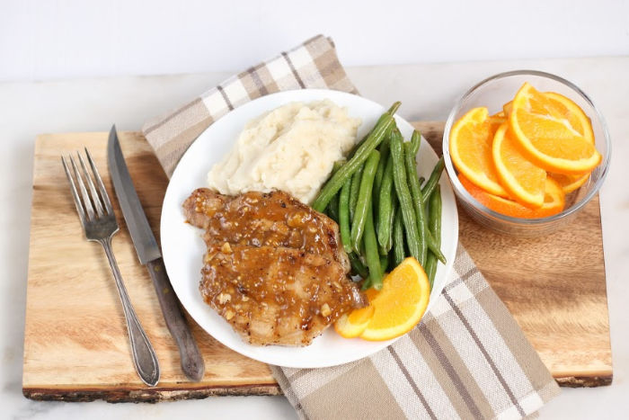 orange glazed pork chops on white plate with fresh green beans and mashed potatoes