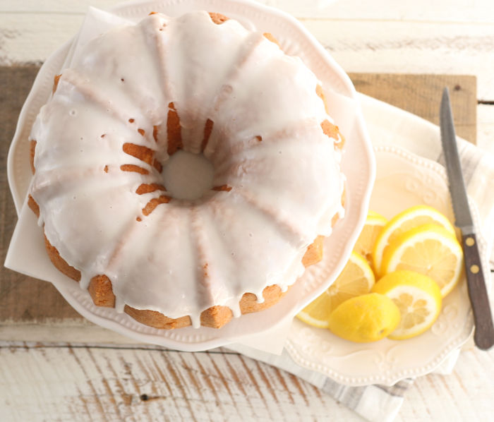 lemon Bundt cake with icing on white footed cake dish, looking down on the cake.