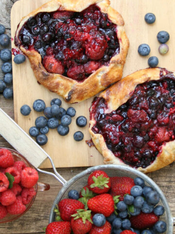 Berry galettes with mixed berries on wooden cutting board.